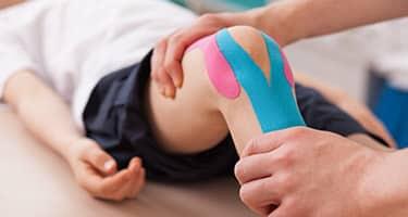 Ein Orthopäde behandelt das getappte Knie eines Kindes