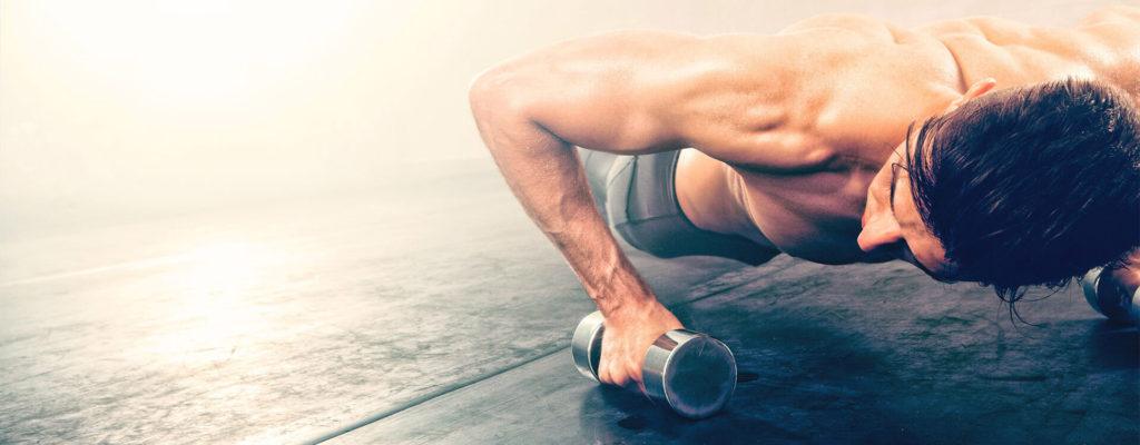 Ein durchtrainierter Mann trainiert seine Schultern durch Liegestützen auf zwei Hanteln am Boden