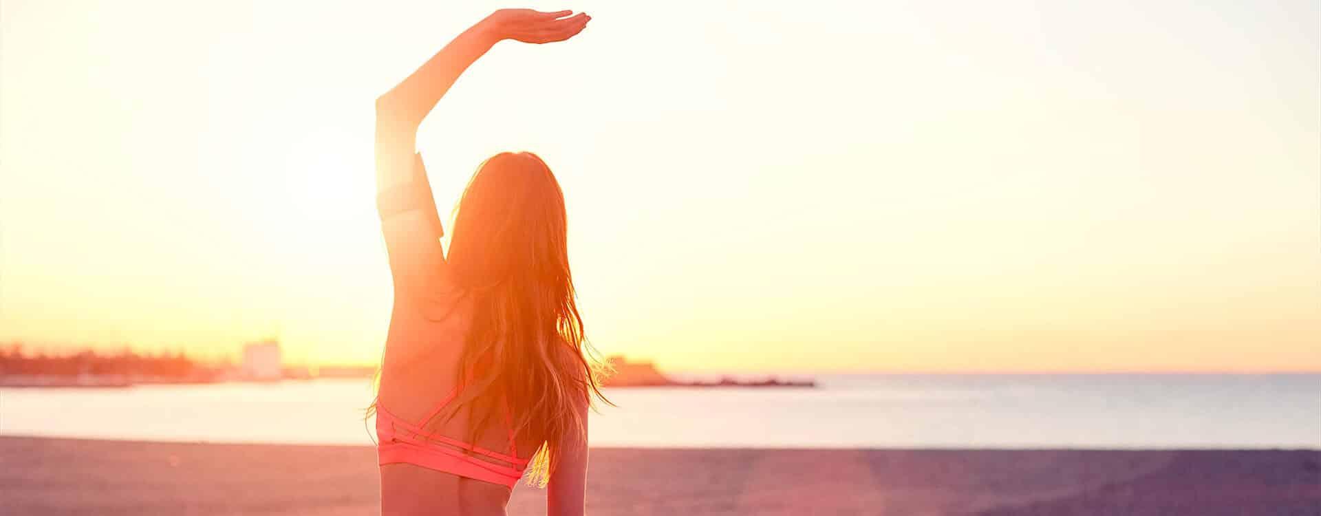 Junge Frau macht Yoga am Strand bei Sonnenuntergang und streckt ihre Wirbelsäule dabei durch