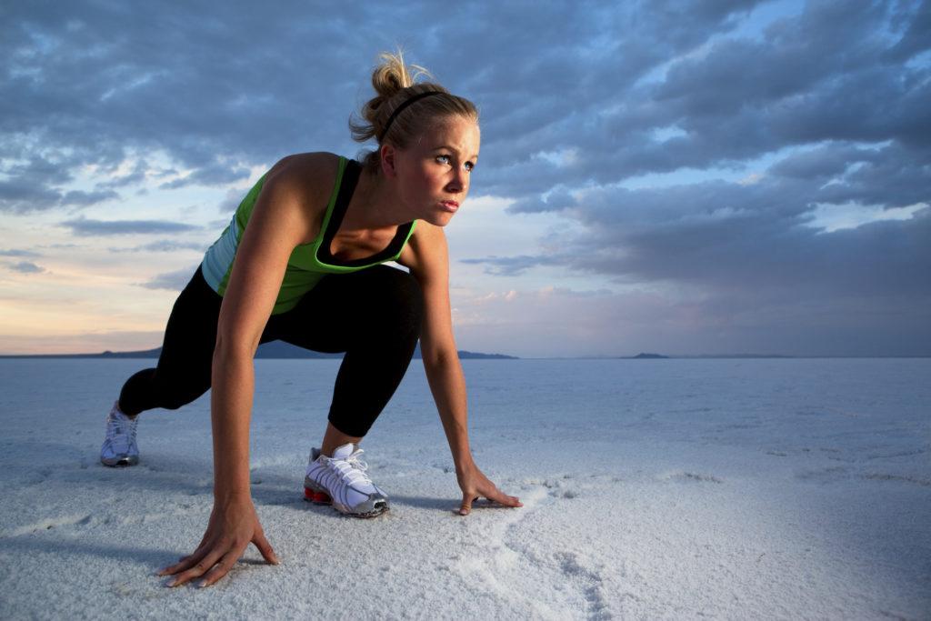 Junge Sportlerin steht in Starthaltung auf einem Salzsee
