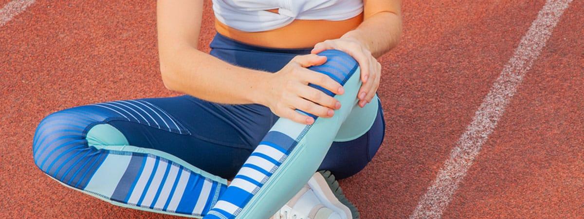 Läuferin sitzt auf dem Boden auf einer Rennbahn und hält sich das linke knie vor Schmerzen
