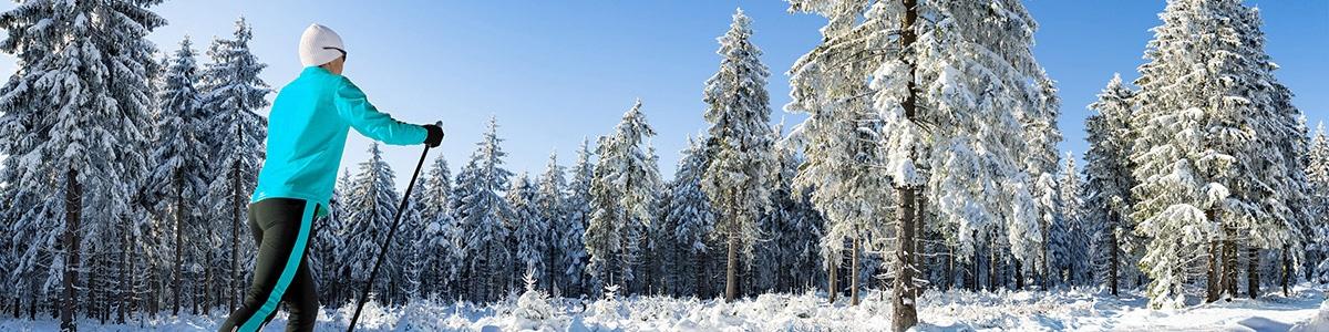 Wintersportverletzungen - Langläufer läuft durch einen verschneiten Wald