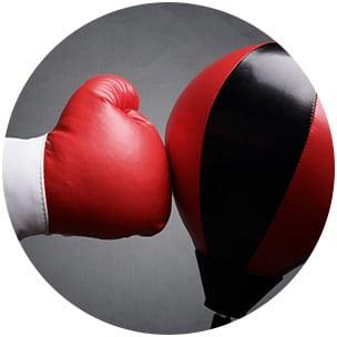 Sinnbild für Direktschaden am Knorpel - Boxhandschuh schlägt auf Punchingball