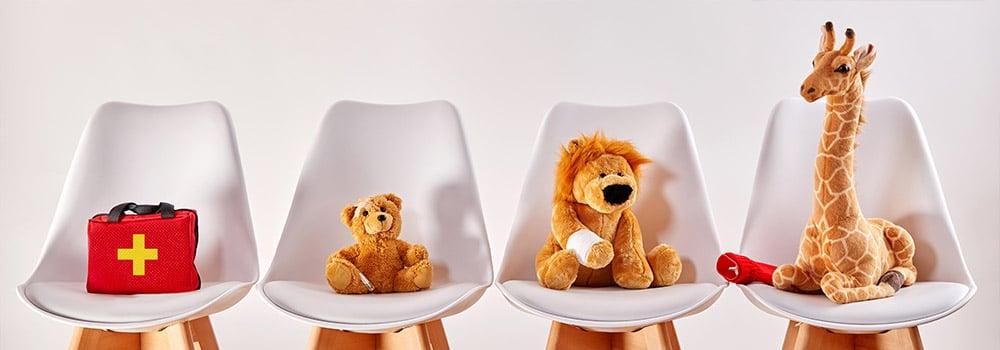 Kinder- und Jugendorthopädie - vier weiße Stühle mit Verbandskasten, Teddybär, Plusch-Löwe mit eingebundener Pfote und Giraffe mit Gips am Bein