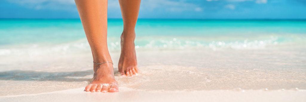 Frau geht barfuß im Sand am Meer