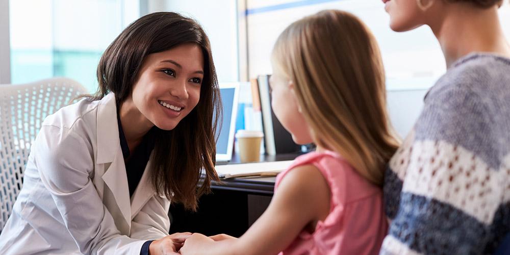 Junge Arzthelferin von Dr. Gründler hält die Hand eines Mädchens vor der Untersuchung auf dem Schoß ihrer Mutter