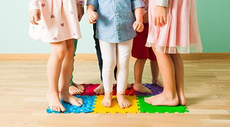Beispielbild für die Köhlerkrankheit - sechs Kinder stehen auf einem Puzzleteppich am Boden