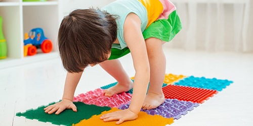 Kind spielt und bewegt sich auf einer Puzzlematte mit verschiedenen Oberflächen bei der Physiotherapie