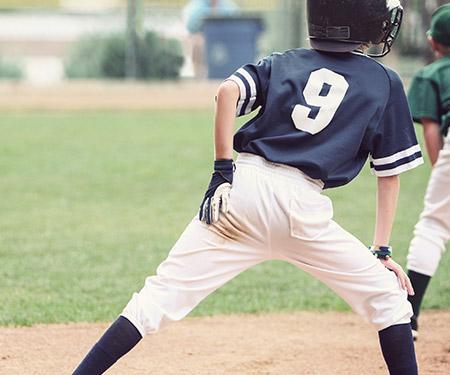 Junger Baseballspieler hält sich die linke Hüfte