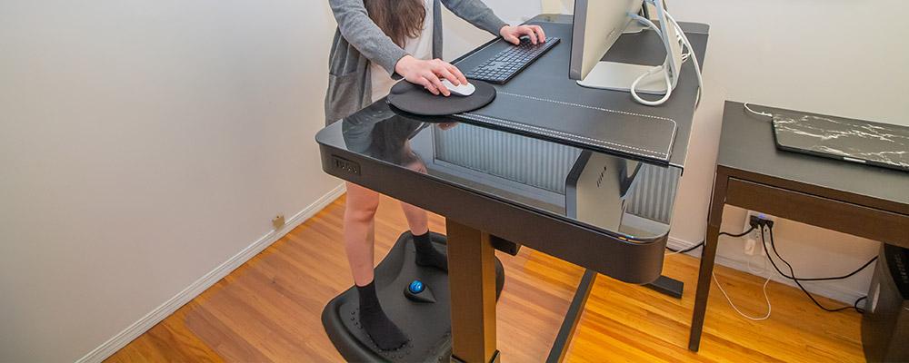 Frau steht auf einem Balanceboard vor Ihrem höhenverstellbaren Stehschreibtisch und arbeitet