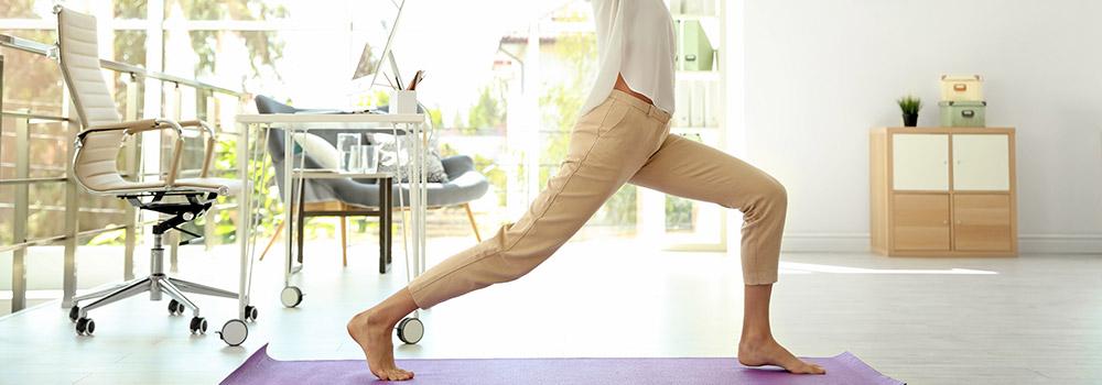 Frau macht Yoga in ihrem Büro, im Hintergrund Schreibtisch und Bürostuhl