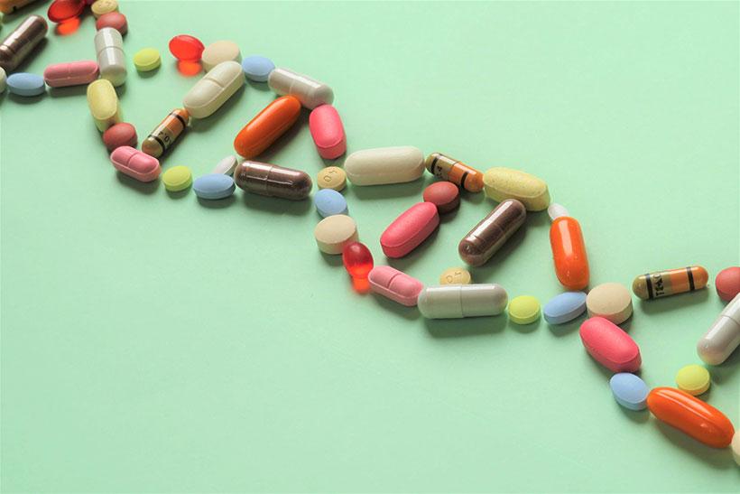 Pharmakogenetik - verschiedenste Tabletten in Form eines DNA Strangs auf grünem Hintergrund
